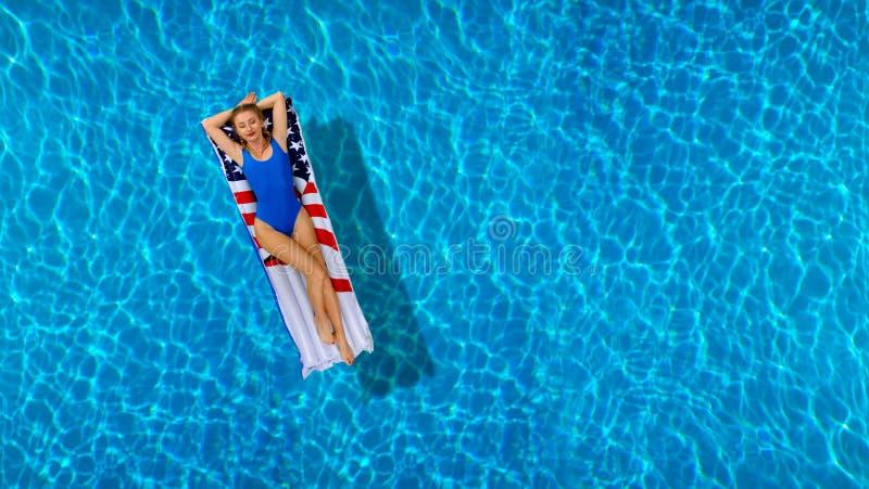 Mujer en bikini en el colchón inflable en la piscina fotografía de archivo