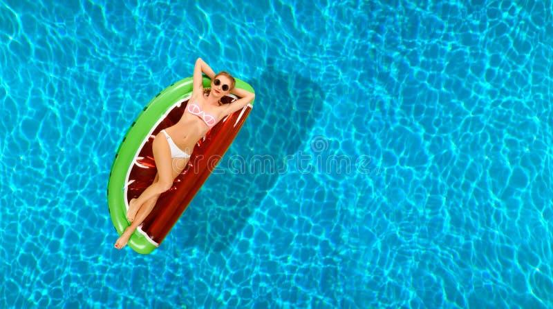 Mujer en bikini en el colchón inflable en la piscina foto de archivo libre de regalías