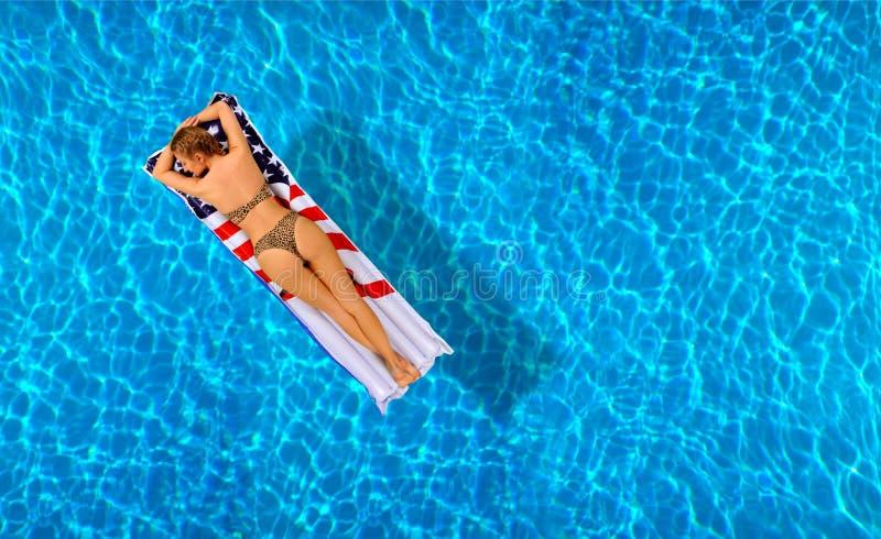 Mujer en bikini en el colchón inflable en la piscina fotos de archivo