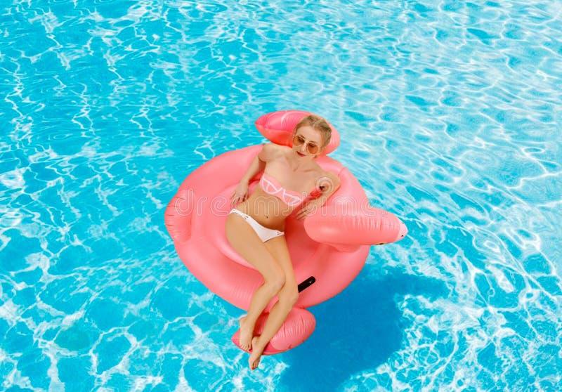 Mujer en bikini en el colchón inflable en la piscina imagen de archivo