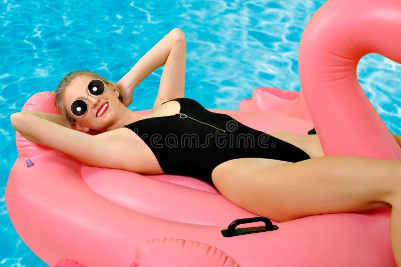 Mujer en bikini en el colchón inflable en la piscina imágenes de archivo libres de regalías