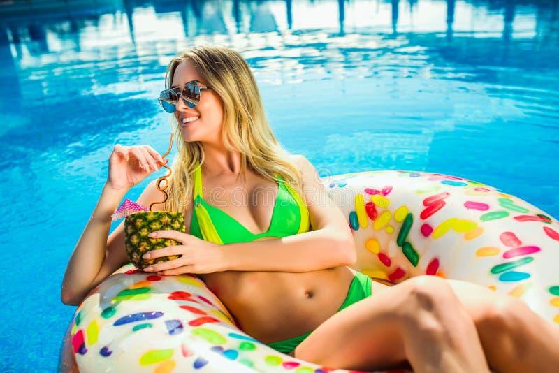 Mujer en bikini en el colchón inflable en la piscina imagenes de archivo