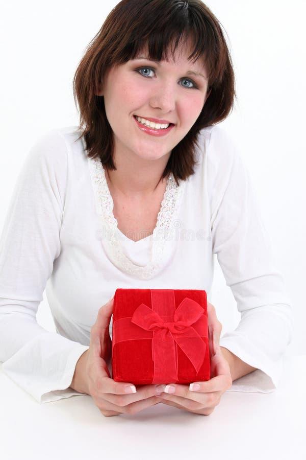 Mujer en blanco con el rectángulo de regalo rojo imagen de archivo