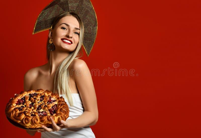 Mujer en bollo sabroso sonriente feliz de la empanada hecha en casa de la cereza dulce del control del casquillo del kokoshnik tr foto de archivo