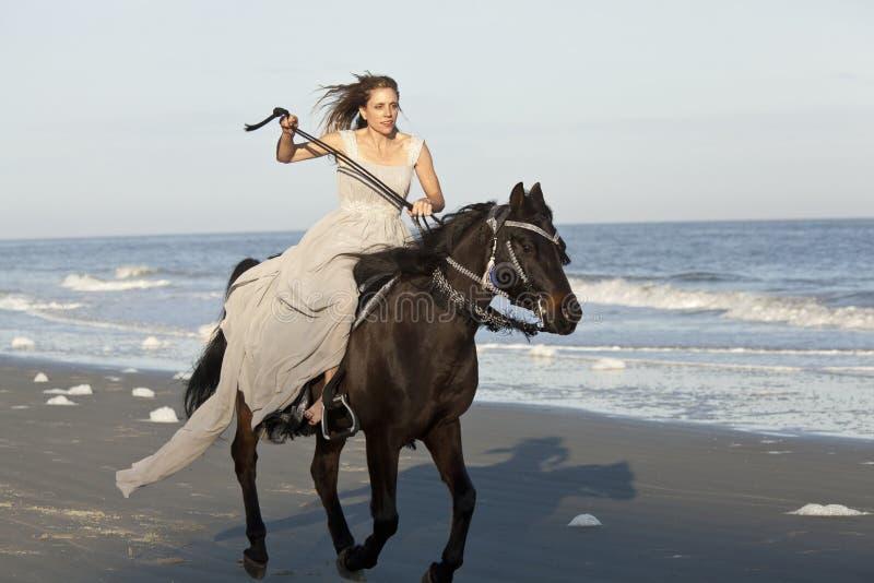 Mujer en caballo galopante en la playa foto de archivo
