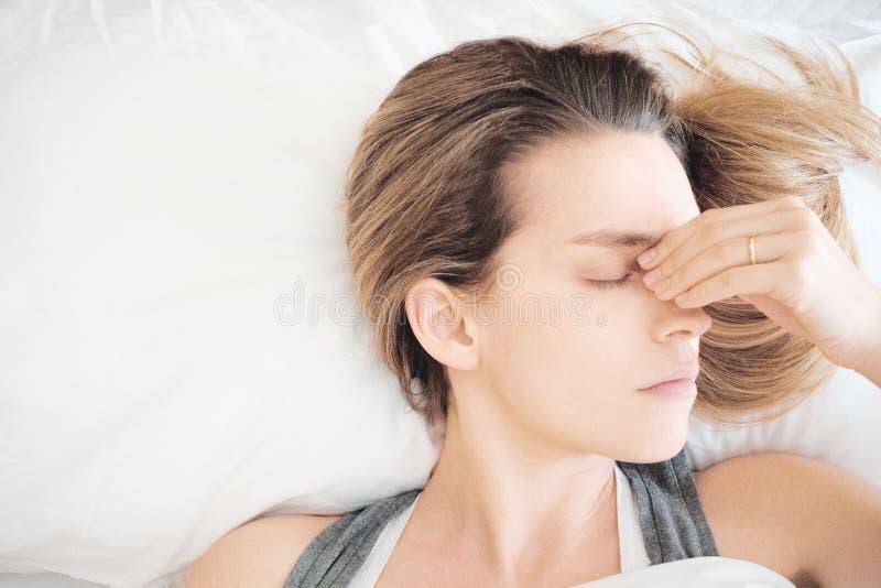 Mujer en cama con alergia o dolor de cabeza foto de archivo libre de regalías