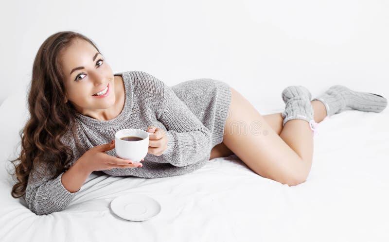 Mujer en cama con café fotografía de archivo