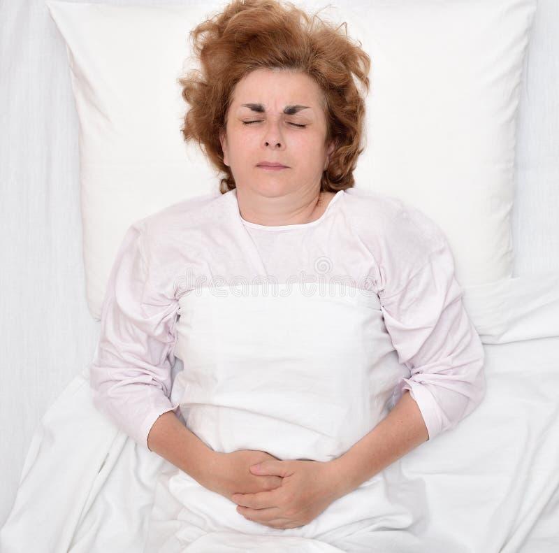 Mujer en cama con el dolor de estómago que se sostiene el estómago foto de archivo libre de regalías