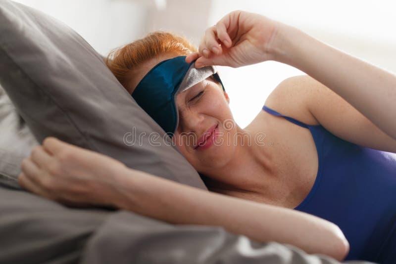 Mujer en cama con la máscara del sueño en los ojos que despiertan foto de archivo