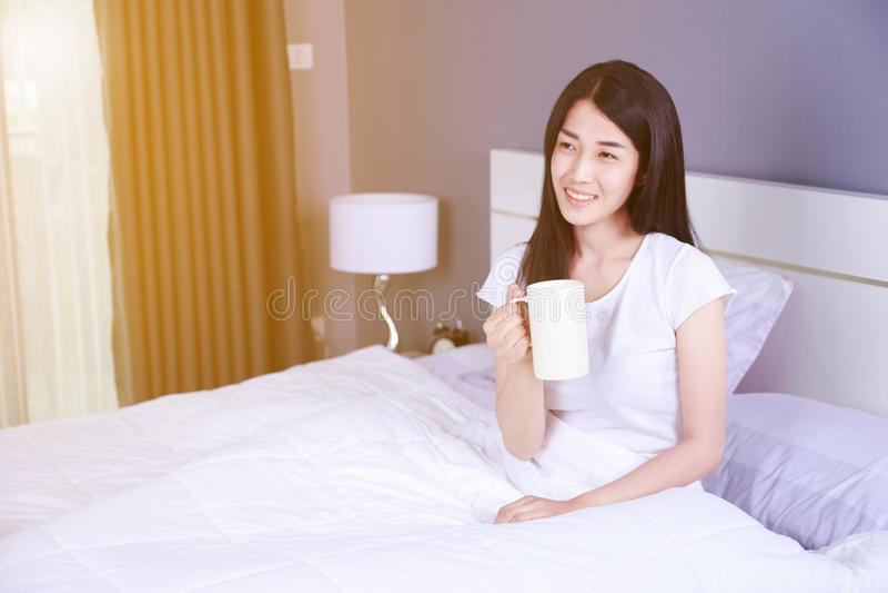 Mujer en cama con una taza de café en dormitorio imagen de archivo