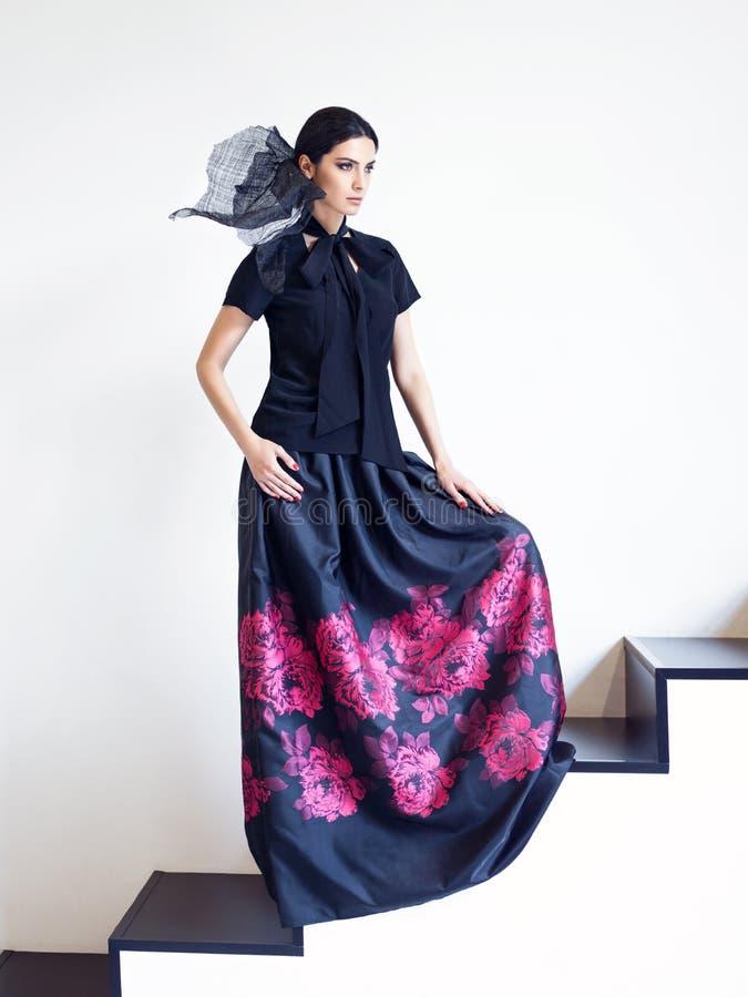 Mujer en camisa negra y falda larga con la impresión floral que presenta en las escaleras fotos de archivo libres de regalías