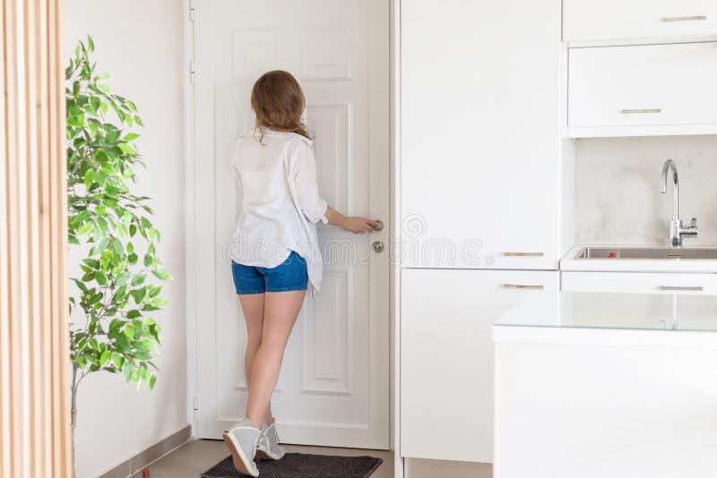 Mujer en camisa y pantalones cortos que miran en puerta de la mirilla cuando alguien suena el timbre fotografía de archivo