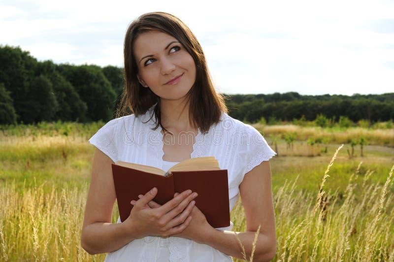 Mujer en campo con el libro imágenes de archivo libres de regalías