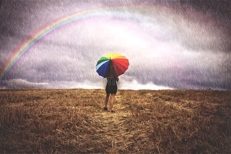 Mujer en campo con el paraguas colorido en la lluvia fotografía de archivo libre de regalías