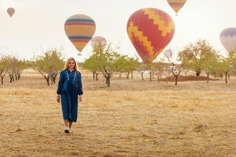 Mujer en campo con el vuelo de los globos del aire caliente en Bakcground imagen de archivo libre de regalías