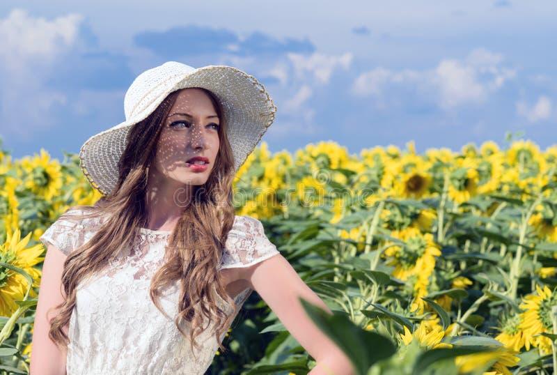 Mujer en campo floreciente del girasol en verano fotos de archivo