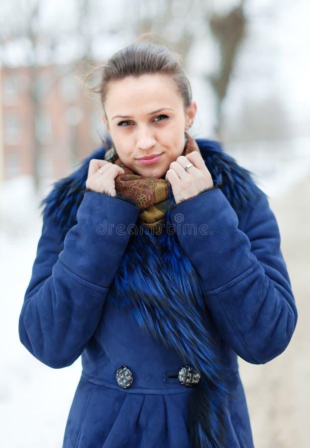 Mujer en capa azul en la calle hivernal de la ciudad imagenes de archivo