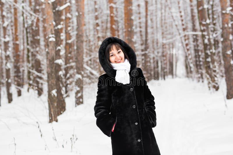 Mujer en capa caliente con la piel en el bosque, día de invierno frío imágenes de archivo libres de regalías