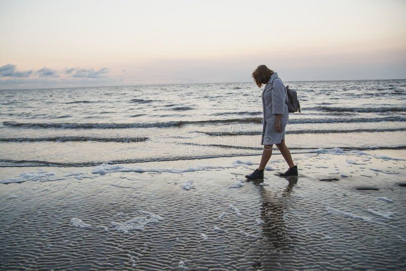 Mujer en capa que camina en la costa fotos de archivo libres de regalías
