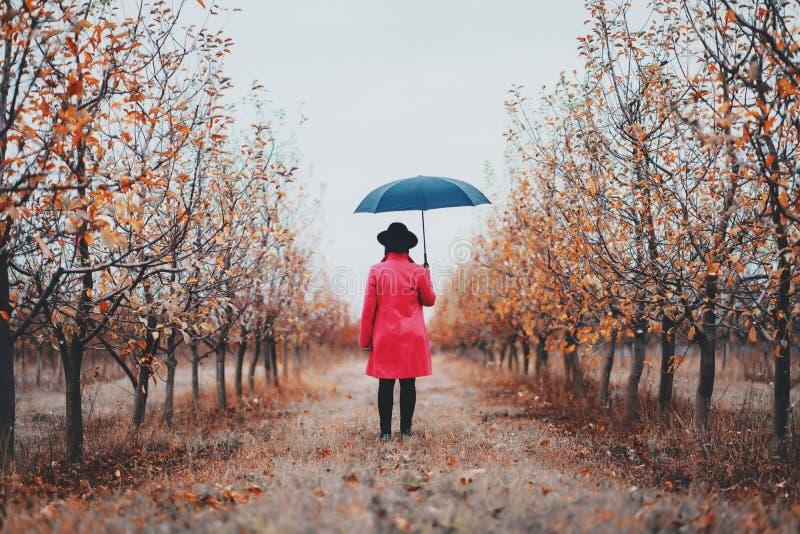 Mujer en capa roja y con el paraguas entre los árboles en jardín de la manzana en la estación del otoño Minimalismo, viaje, conce imágenes de archivo libres de regalías
