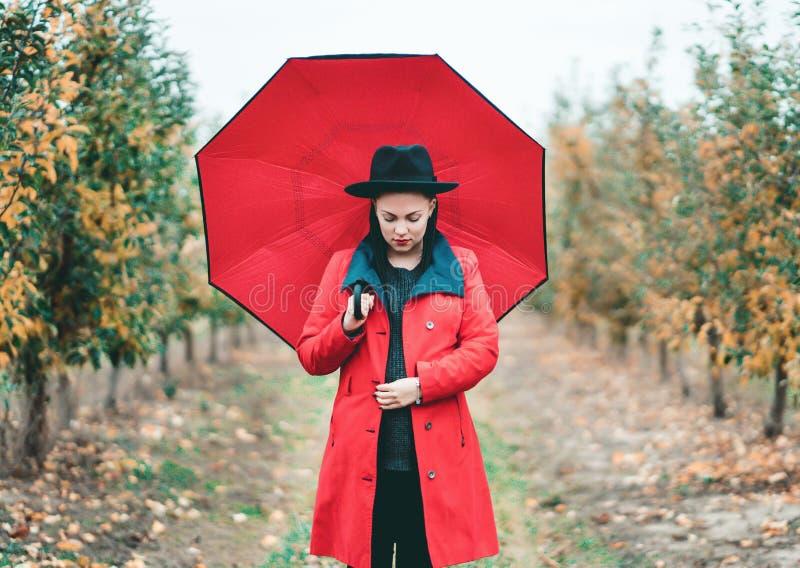 Mujer en capa roja y con el paraguas entre los árboles en jardín de la manzana en la estación del otoño Retrato hermoso de la muc foto de archivo