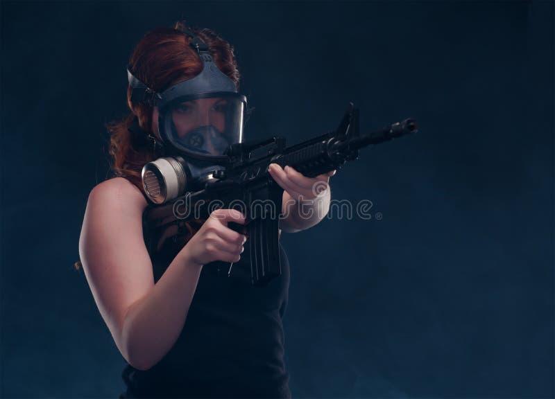 Mujer en careta antigás con un rifle de asalto fotografía de archivo libre de regalías