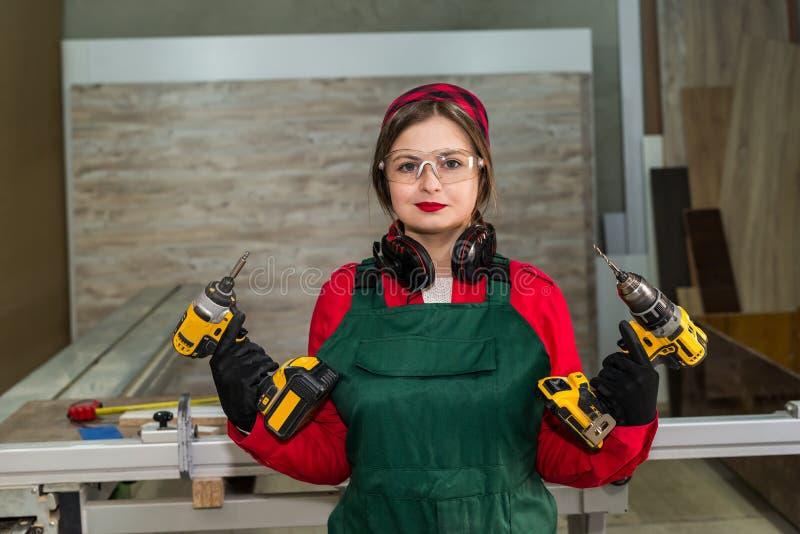 Mujer en carpintería con las máquinas del taladro foto de archivo