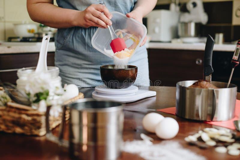 Mujer en casa que cuece la torta imagenes de archivo