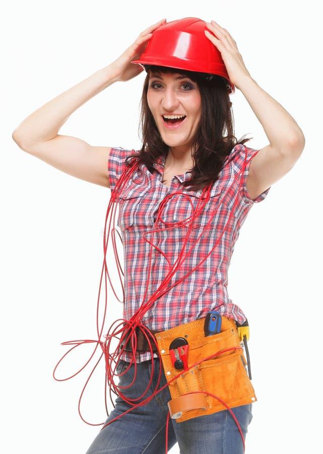 Mujer en casco con el cable rojo enredado fotografía de archivo