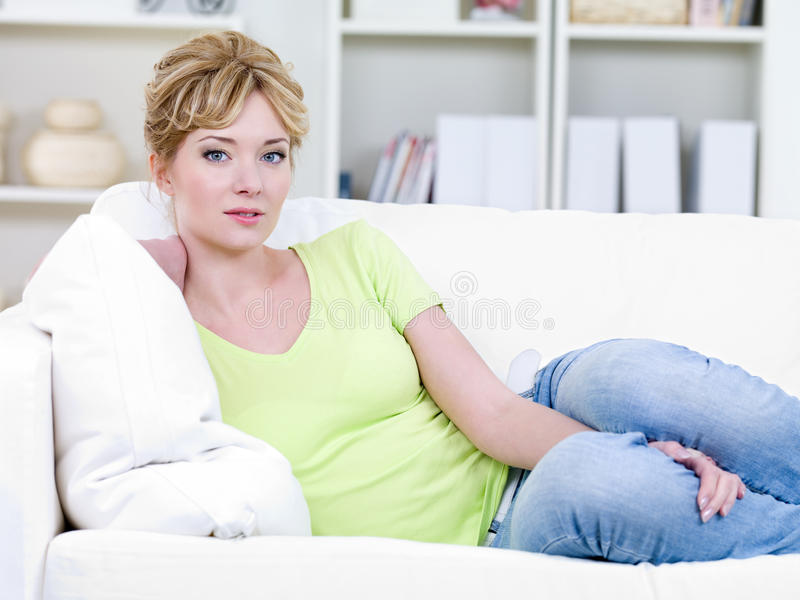 Mujer en casuals en el sofá fotos de archivo libres de regalías