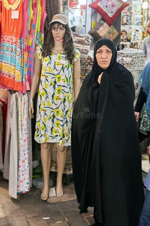 Mujer en chador cerca del maniquí que lleva el vestido corto, Teherán, Irán fotografía de archivo libre de regalías