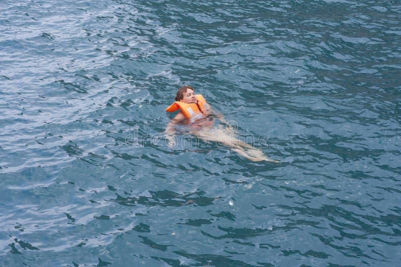 Mujer en chaleco salvavidas anaranjado en agua de un mar imagen de archivo
