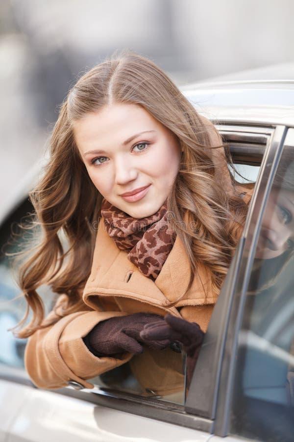 Mujer en coche. Mujer joven hermosa que mira hacia fuera de un coche y de un l imagen de archivo libre de regalías