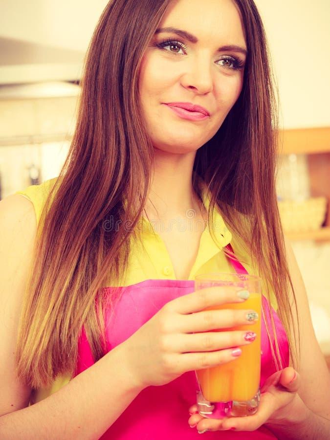 Mujer en cocina que bebe el zumo de naranja fresco foto de archivo libre de regalías