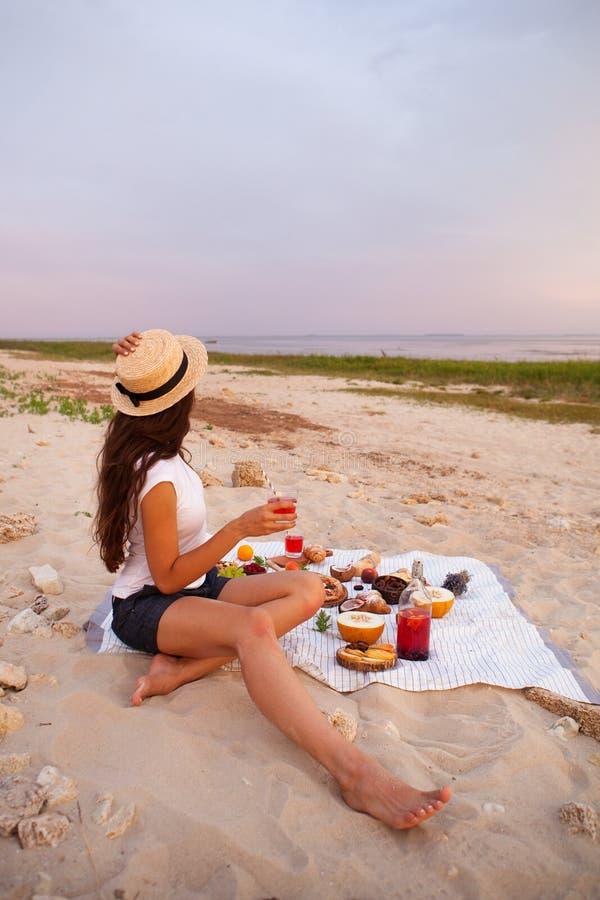 Mujer en comida campestre del verano en la playa en la puesta del sol en la tela escocesa blanca foto de archivo libre de regalías