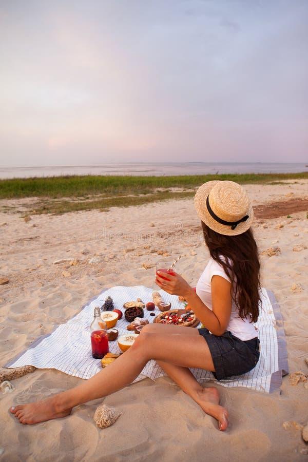 Mujer en comida campestre del verano en la playa en la puesta del sol en la tela escocesa blanca foto de archivo