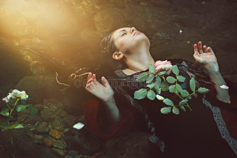 Mujer en corriente oscura del agua y luz del sol suave imagen de archivo libre de regalías