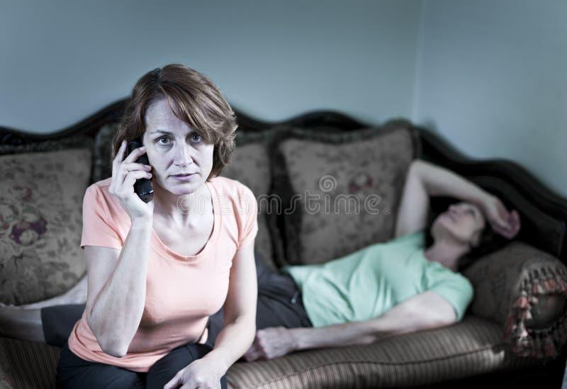 Mujer en cuestión con la madre enferma imágenes de archivo libres de regalías