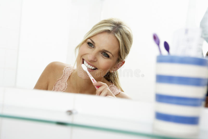 Mujer en dientes que aplican con brocha del cuarto de baño foto de archivo libre de regalías