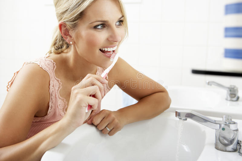 Mujer en dientes que aplican con brocha del cuarto de baño imagenes de archivo