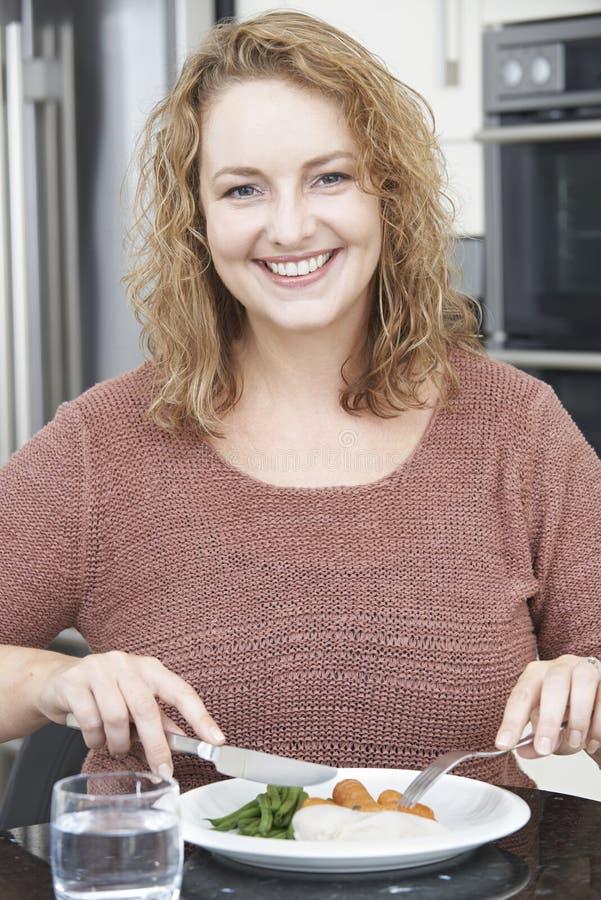 Mujer en dieta que come la comida sana en cocina foto de archivo
