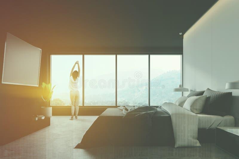 Mujer en dormitorio principal gris con la TV imágenes de archivo libres de regalías