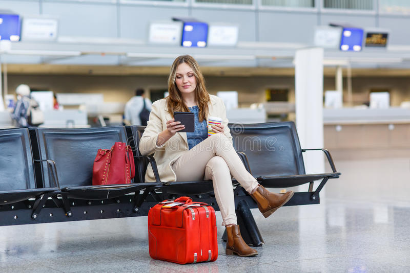 Mujer en el aeropuerto internacional, leyendo el ebook y bebiendo el coffe imágenes de archivo libres de regalías