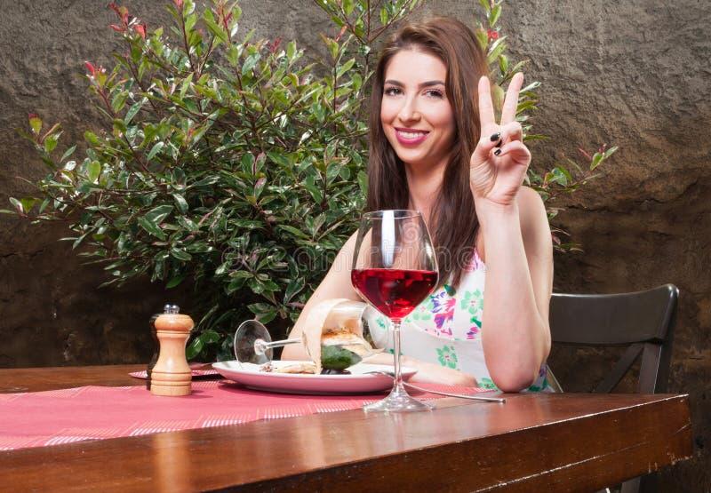 Mujer en el almuerzo en la terraza que muestra el signo de la paz imágenes de archivo libres de regalías