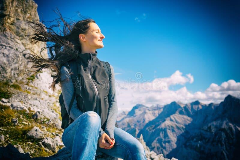 Mujer en el alza de la montaña que descansa, su pelo que sopla en viento imagenes de archivo