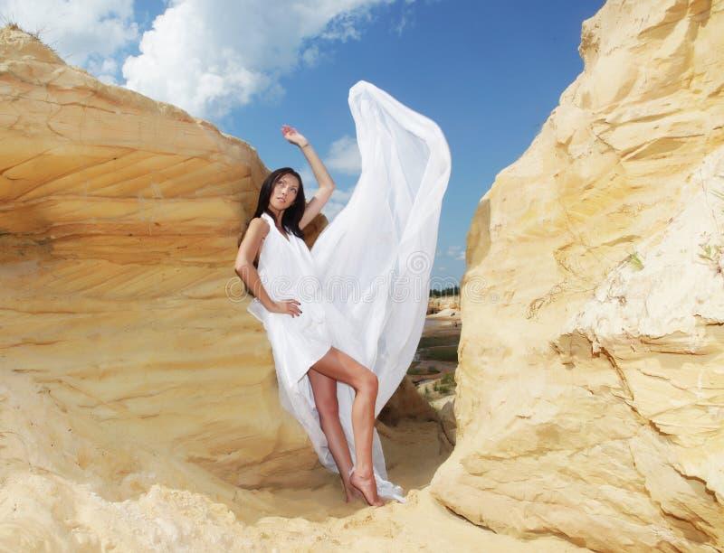 Mujer en el baile blanco del vestido en el desierto foto de archivo