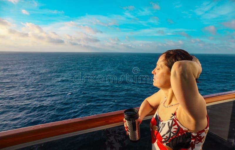Mujer en el balcón de un barco de cruceros en la salida del sol fotografía de archivo