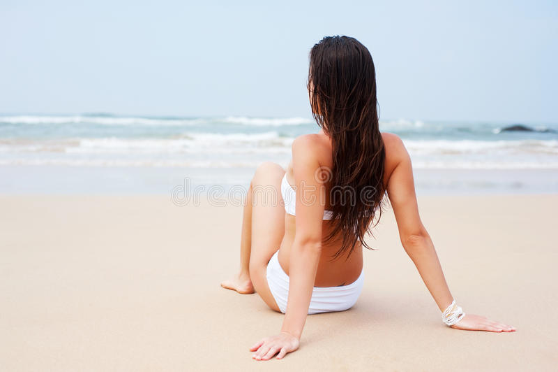 Mujer en el bikiní blanco que se sienta en la playa fotos de archivo