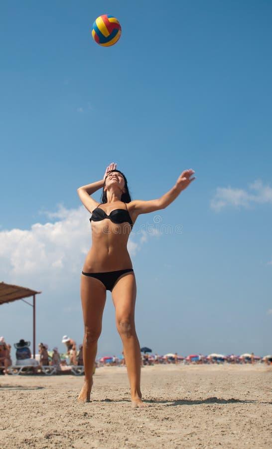 Mujer en el bikiní que juega a voleibol al aire libre imagen de archivo libre de regalías