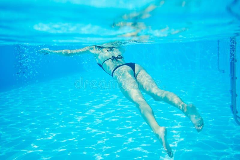 Mujer en el bikini negro que flota en la piscina, foto bajo el agua foto de archivo libre de regalías